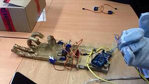 Student bewegt Roboterhand über einen Handschuh